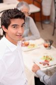 Young waiter serving lunch