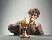 Young man looking at the artificial globe. Adventurer and explorer concept. Geography. poster