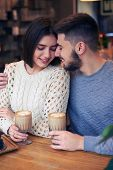 Vertical of affectionate young couple looking at each other at cafe poster