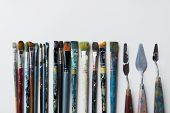 fine art, creativity and artistic tools concept - palette knives or painting spatulas and paintbrush poster