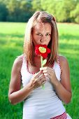 Portrait Of Young Woman With Plushy Flower In Hand