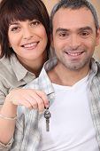 Mid life couple with the keys to their new home