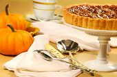stock photo of pumpkin pie  - Pecan pie with small pumpkins on the table