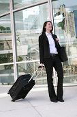 picture of flight attendant  - A pretty business woman travelling with a suitcase - JPG
