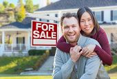 Mixed Race Caucasian and Chinese Couple In Front of For Sale Real Estate Sign and House. poster