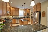 stock photo of granite  - spacious modern kitchen with maple cabinets and granite - JPG