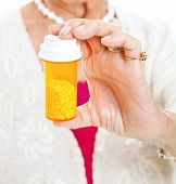 Closeup of a bottle of prescription pills in the hand of a senior woman.