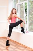 Young Woman Does Stretching Exercise In Gym By The Window