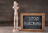 Wooden figure and chalkboard with text Stop bullying on table poster