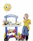 An adorable preschooler by her flower stand happily displaying a fist full of money and a calculator