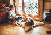 Boy Reading Book On The Floor Near Slipping His Beagle Dog On Sheepskin In Cozy Home Atmosphere. Pea poster
