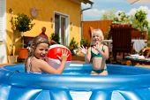 Kinder - sind sie Schwestern - spielen im Wasser mit einem Ball im Garten vor dem Haus
