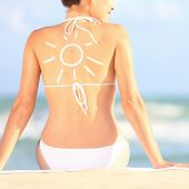 Sunscreen / sun tan lotion sun drawing on woman back. Girl in bikini sitting on beach in sunlight.