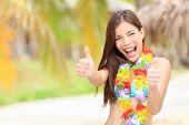 Vacation summer fun woman showing thumbs up smiling happy in joyful bliss. Pretty mixed race Asian / Caucasian female bikini model cheerful on beach.