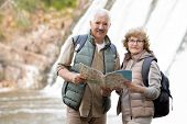 Happy senior couple with backpacks and map standing in front of camera with waterfalls behind while  poster