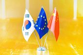Three Flags On The Table. Flags Of South Korea, European Union And China. Flags Of South Korea, Euro poster