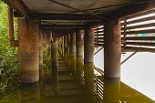 Rusty Metal Columns Of The Base Of A Wooden Pier In The Water Of A River In Summer. View Under The P poster