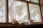 A White Cup And Old Books On The Background Of A Rustic Wooden Wet Window, Copy Space. Hot Drink For poster