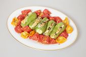 Oven baked tomatoes and courgettes, the latter stuffed with soft goat's cheese.