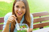 Happy Smiling Woman Eating Salad Sitting In The Park Looks At Camera With Copy Space Area. Lunch Sal poster