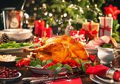 Christmas turkey dinner. Baked turkey garnished with red berries and sage leaves in front of Christm poster