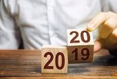 Two Wooden Blocks With Numbers 2019 And 2020. The Concept Of The Beginning Of The New Year. New Obje poster