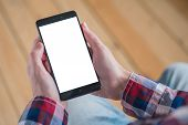 Mockup Image: Man Looking At Black Smartphone With White Blank Screen. Close Up View Of Man Hands Wi poster