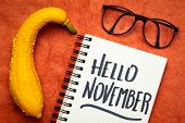Hello November - cheerful handwriting in a notebook with a decorative gourd poster