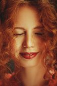 Happy girl with beautiful red curly hair is smiling with closed eyes. Close-up portrait. Hair care,  poster