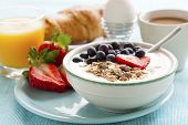 stock photo of cereal bowl  - Bowl of muesli with yoghurt strawberries and blueberries boiled egg orange juice croissant and coffee for healthy breakfast - JPG