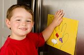 Child putting his art up on family refrigerator at home