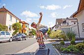 Постер, плакат: Мальчик верхом происходит воздушно на тротуаре скейтборд