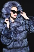 A portrait of a beautiful woman wearing a fur coat with hood and sunglasses. Beauty, winter fashion, poster