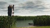 picture of marshlands  - Mediaeval or fantasy tower in empty marshlands with depth of field effect to focus on tower - JPG