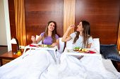Two Pretty Girls Eating In Bed poster