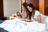 Beautiful Young Women Eating In Bed poster