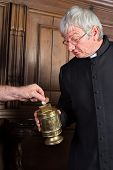 Priest collecting money in church for fund-raising