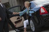 Chauffeur helps woman to get down from luxury car