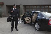 Mixed race chauffeur holding golf equipments next to luxury car