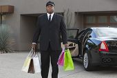 Mixed race chauffeur holding shopping bags by luxury car