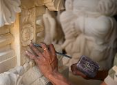 stock photo of mason  - Stone mason at work carving an ornamental relief - JPG