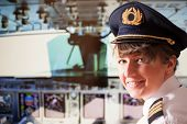 Beautiful woman pilot wearing uniform with epaulets, hat with golden wings sitting inside airliner w