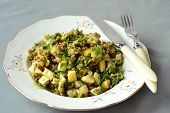 A plate with a salad of lentils and pears and parsley on a gray background