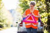 Young female driver wearing a high visibility vest, setting up the reflective trianglec after her ca