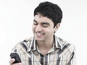 Asian Male Of Indian Origin Looking At His Cell Phone