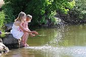 image of squirting  - young mother and her little daughter squirting water at the lake - JPG
