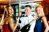 Good friends - bartender and women - with a large magnum bottle champagne at bar having fun, she pul