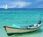 A fishing boat with a sail boat in the backgrund on a tropical blue sea.