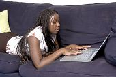 Teen Laying Down On Couch With Laptop