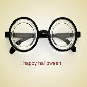 picture of short-sighted glasses and the sentence happy halloween on a beige background, with a retr